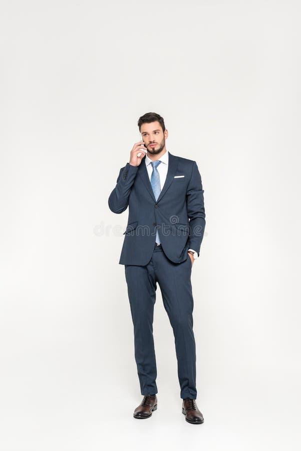 de volledige lengtemening van modieuze jonge zakenman status met dient zak en het spreken op smartphone in royalty-vrije stock afbeelding