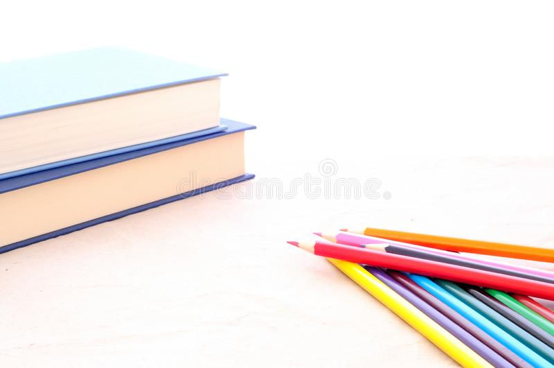 De volta à escola, ao fundo minimalista, aos lápis coloridos e aos livros imagens de stock royalty free