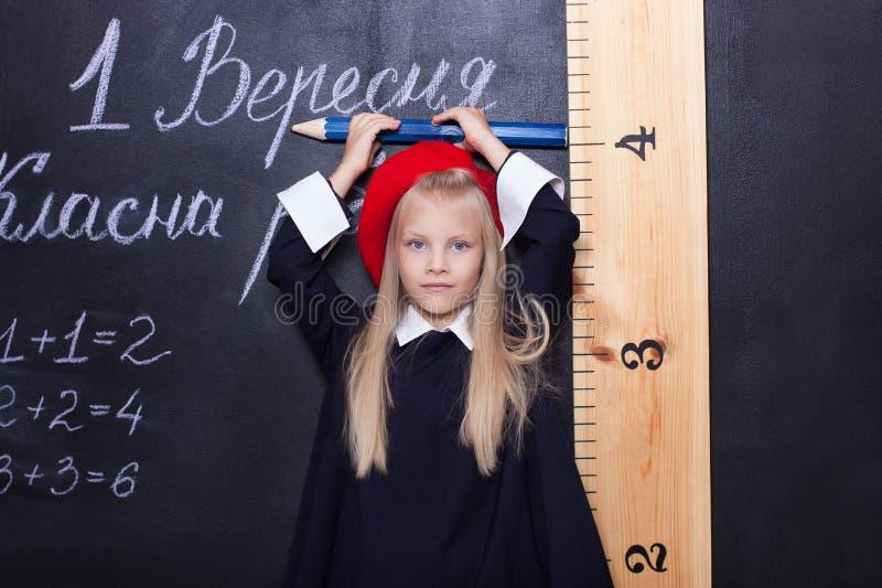 De volta à escola! A estudante está no quadro-negro com uma régua A estudante responde à lição Primeiro graduador perto da placa  fotografia de stock royalty free