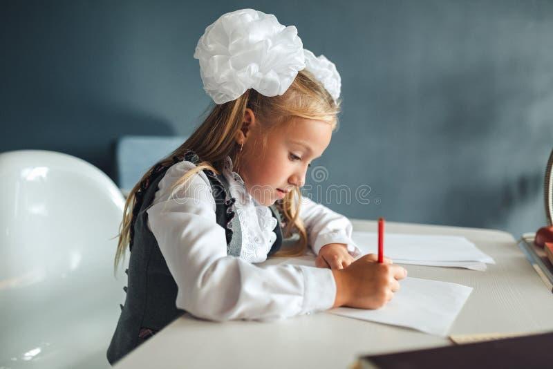 De volta à escola, menina bonito que pinta uma imagem na casa, escrita da menina no caderno com o lápis em seu quarto Estudante c imagens de stock royalty free