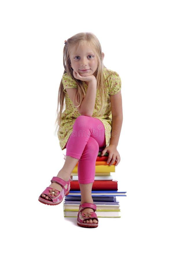 De volta à escola. Menina que senta-se em uma pilha de livros fotos de stock