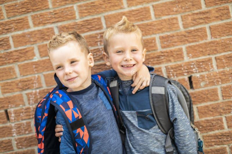 A de volta à escola Rapaz pequeno dois feliz com trouxa imagem de stock