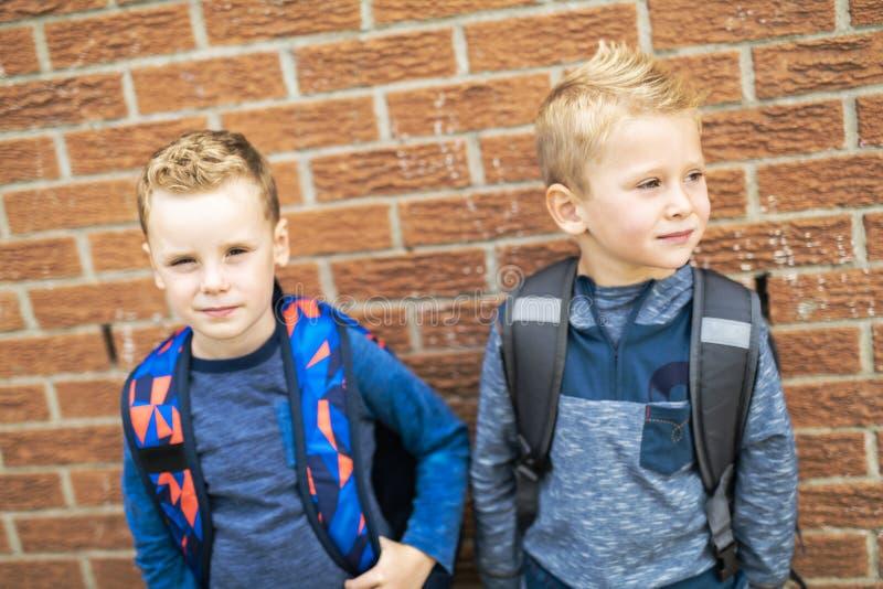 A de volta à escola Rapaz pequeno dois feliz com trouxa fotos de stock