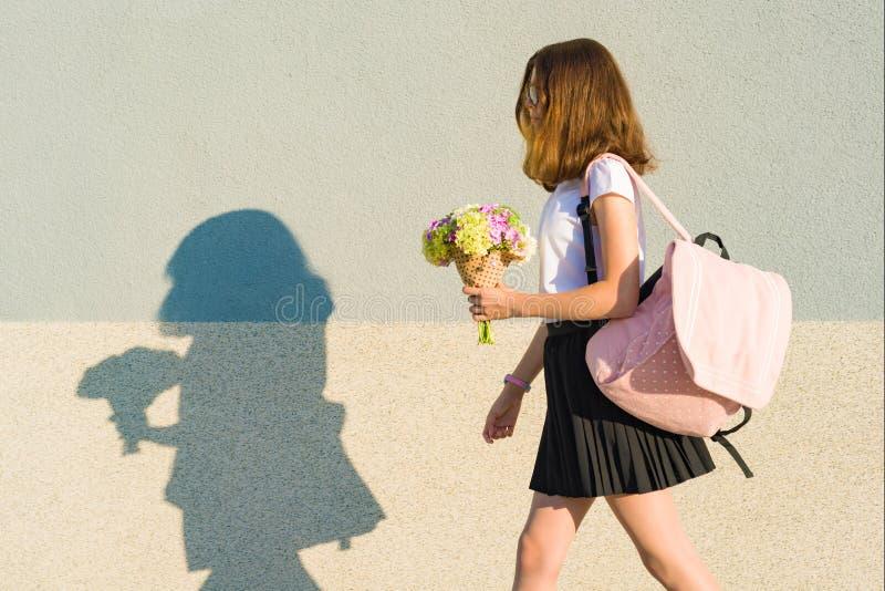 De volta à escola Retrato exterior do adolescente feliz com trouxa, flores, espaço da cópia fotografia de stock royalty free
