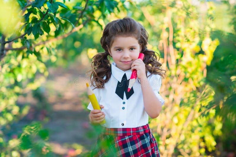 De volta à escola Uma estudante bonito está guardando lápis em suas mãos, sorrindo na câmera Educação O conceito do anúncio fotos de stock royalty free