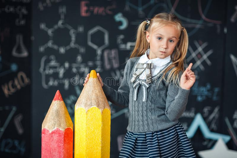 De volta à escola! Uma menina loura pequena em suportes da farda da escola com os dois muito grandes lápis no floore contra o qua foto de stock royalty free