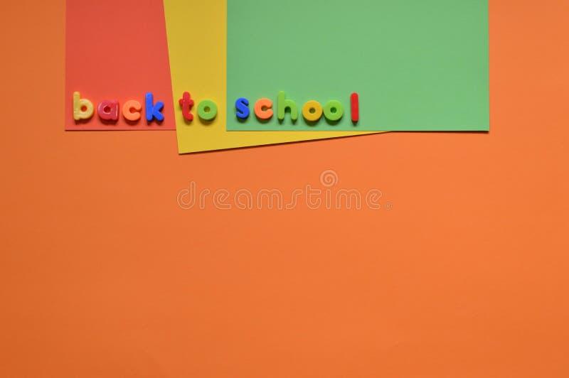 DE VOLTA às letras da ESCOLA no cartão colorido imagem de stock royalty free