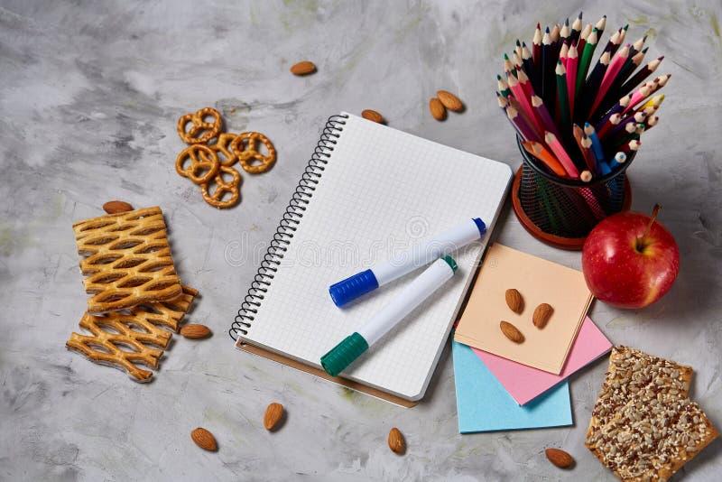 De volta ao conceito da escola, às fontes de escola, aos biscoitos e à cesta de comida na mesa branca, foco seletivo, close-up fotos de stock royalty free
