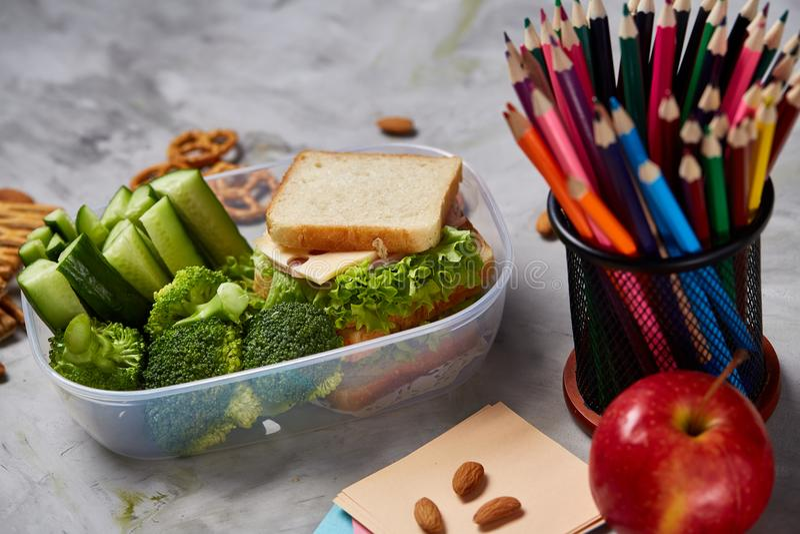 De volta ao conceito da escola, às fontes de escola, aos biscoitos e à cesta de comida na mesa branca, foco seletivo, close-up foto de stock royalty free