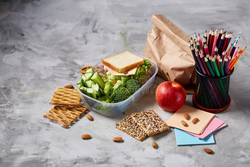 De volta ao conceito da escola, às fontes de escola, aos biscoitos e à cesta de comida na mesa branca, foco seletivo, close-up imagens de stock