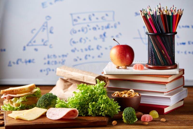 De volta ao conceito da escola, às fontes de escola, aos biscoitos e à cesta de comida sobre o quadro branco, foco seletivo, clos imagens de stock