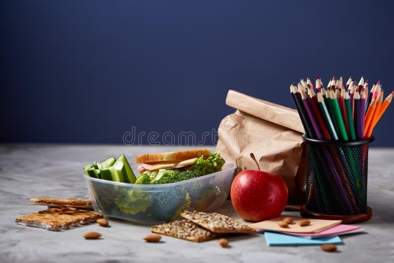 De volta ao conceito da escola, as fontes de escola, biscoitos, embalaram o almoço e a cesta de comida na mesa branca, foco selet fotografia de stock royalty free