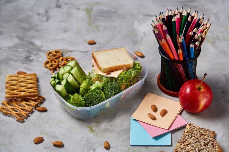 De volta ao conceito da escola, as fontes de escola, biscoitos, embalaram o almoço e a cesta de comida sobre o quadro branco, foc foto de stock royalty free