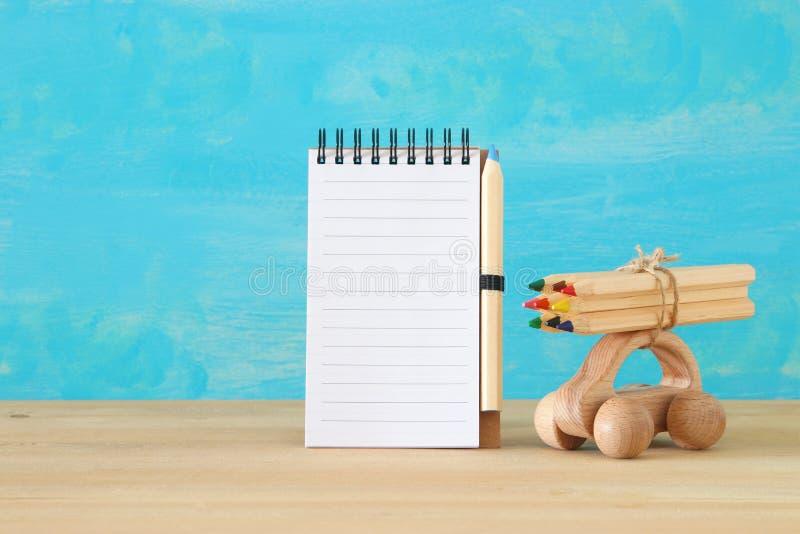 De volta ao conceito da escola Carro de madeira do brinquedo com os lápis coloridos no telhado ao lado do caderno vazio Para a zo fotografia de stock