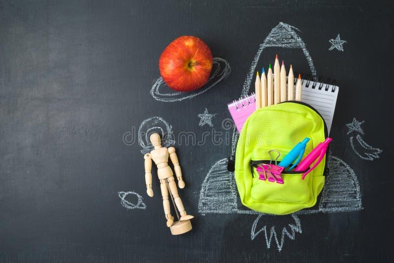 De volta ao conceito da escola com a trouxa do saco, fontes de escola e esboço pequenos do foguete sobre o fundo do chalkboad Vis fotografia de stock