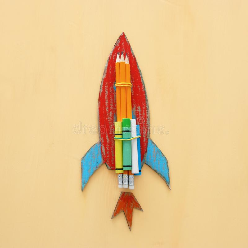 De volta ao conceito da escola corte do foguete do cartão do papel e pintado sobre o fundo amarelo de madeira fotografia de stock