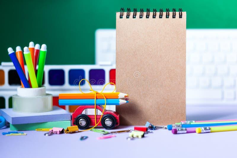 De volta ao conceito da escola Escola e materiais de escritório, penas coloridas, lápis, pinturas no fundo verde foto de stock