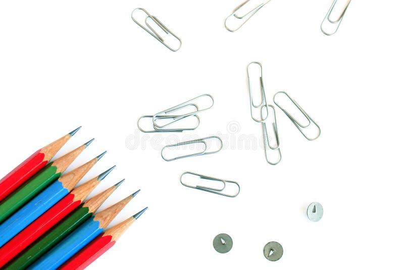 De volta ao conceito da escola Grupo de lápis coloridos, de grampos e de percevejos no fundo branco ilustração stock