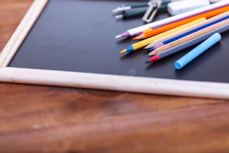 De volta ao conceito da escola, lápis coloridos na tabela preta, acessórios coloridos dos artigos de papelaria para a criança do  fotos de stock