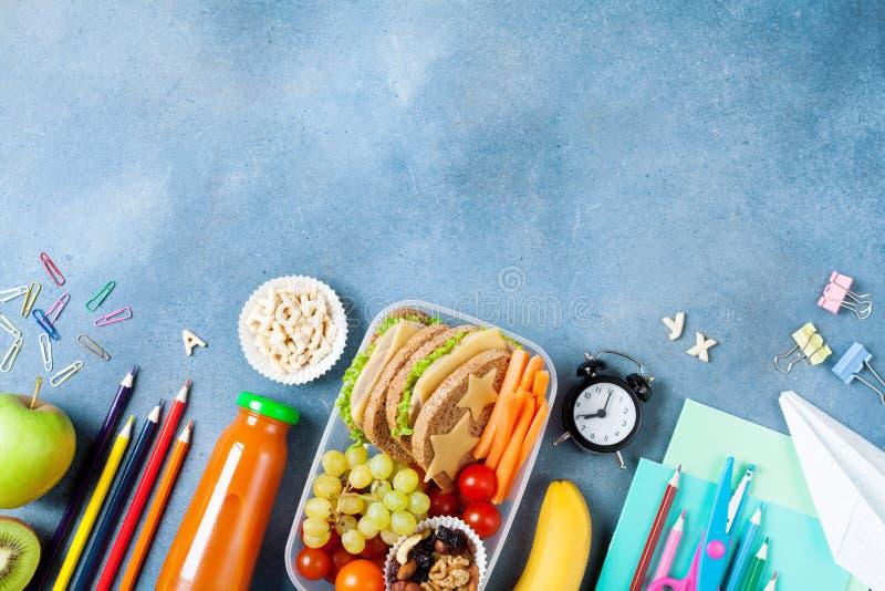 De volta ao conceito da escola Lancheira saudável e artigos de papelaria coloridos na opinião de tampo da mesa azul imagem de stock royalty free