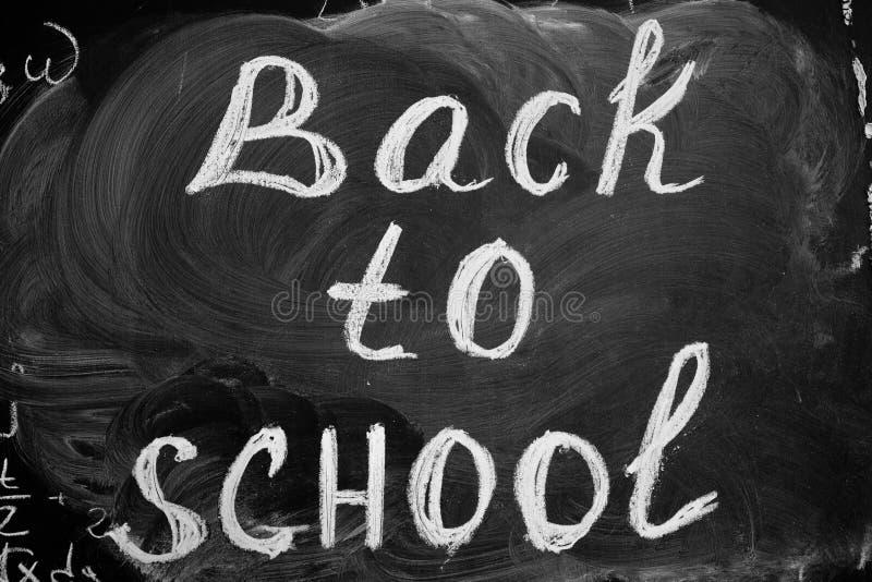 De volta ao fundo da escola com ` do título de volta ao ` da escola escrito pelo giz branco no quadro preto fotografia de stock