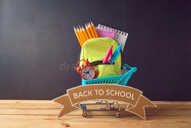 De volta ao fundo da escola com fontes pequenas da trouxa e de escola do saco na tabela de madeira foto de stock royalty free