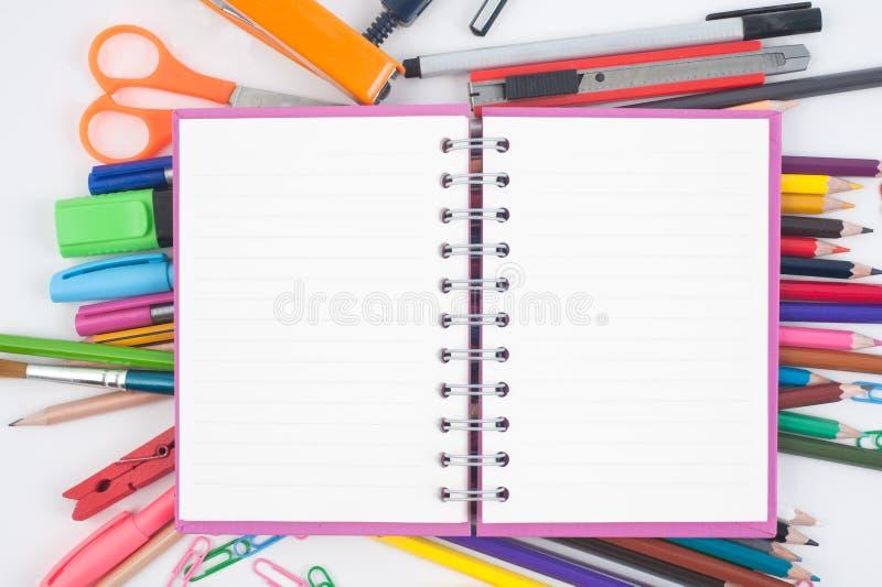 De volta ao livro do esboço da placa da escola e às ferramentas coloridas da escola no fundo branco imagens de stock