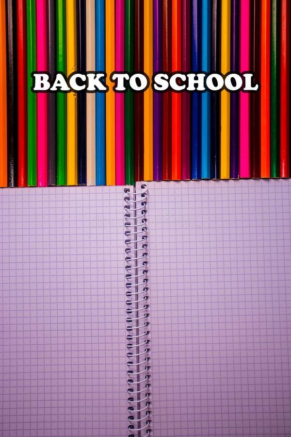 De volta ao texto de escola em lápis coloridos brilhantes com caderno branco foto de stock