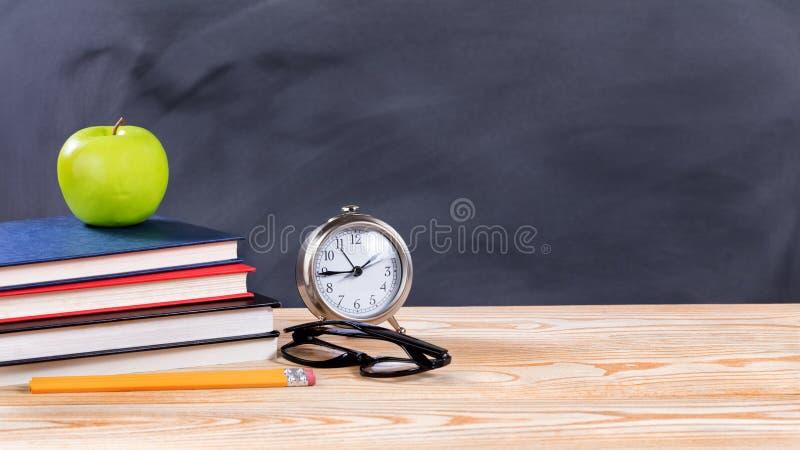 De volta aos objetos da escola na frente do quadro preto apagado fotografia de stock royalty free