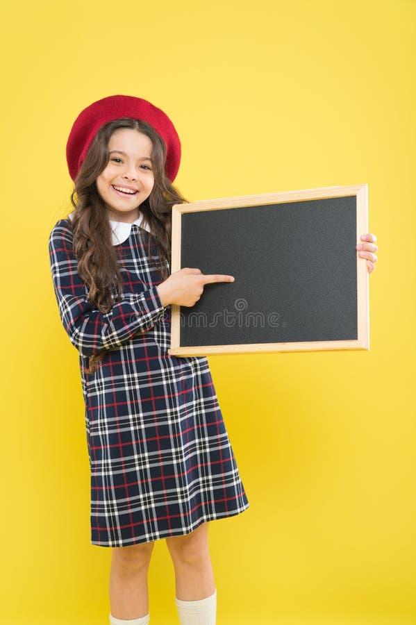 De volta ? escola Aluno pequeno que aponta o dedo no quadro-negro vazio no fundo amarelo Estudante pequena bonito com fotos de stock
