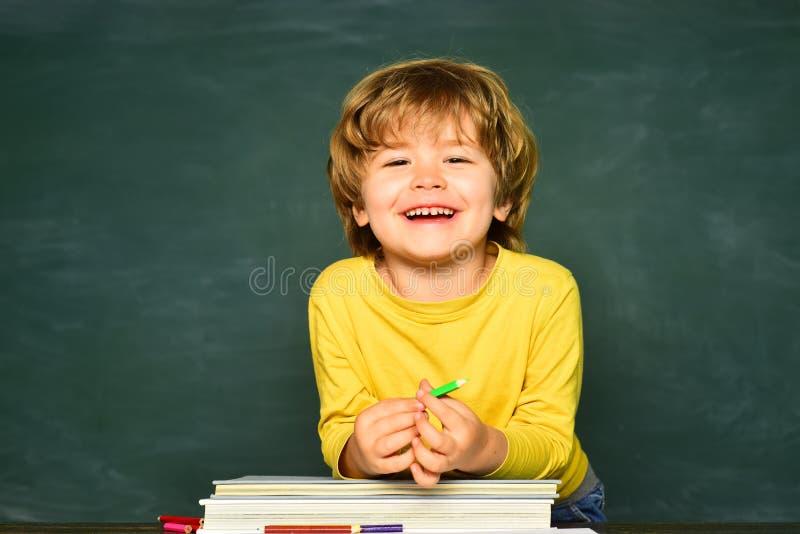 De volta ? escola e ao tempo feliz O aluno ou a crian?a em idade pr?-escolar aprendem Conceito da educa??o e da leitura Escola da imagens de stock