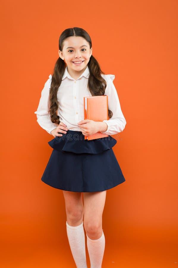 De volta ? escola Menina pequena adorável que aprecia seu tempo da escola no fundo alaranjado Estudante pequena feliz que tem fotos de stock