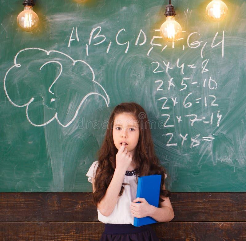 De volta ? escola schoolgirl Conceito da escola Menina de sorriso, escrevendo o texto no quadro-negro Pouco primeiros graduadores imagens de stock