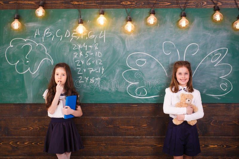 De volta ? escola schoolgirl Li??es da escola Pouco primeiros graduadores Livro de leitura feliz da menina da criança De volta ?  fotos de stock