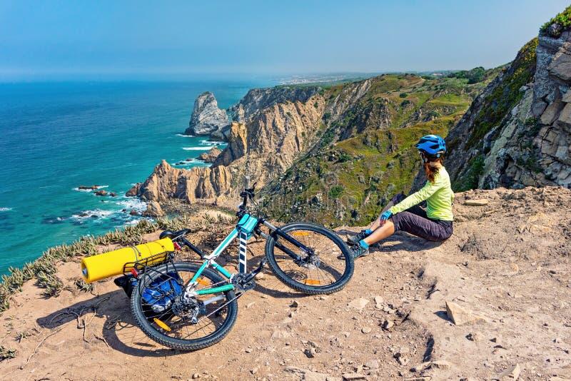 De volwassen aantrekkelijke vrouwelijke fietser met haar bergfiets zit op een oceaan rotsachtige kust stock afbeelding