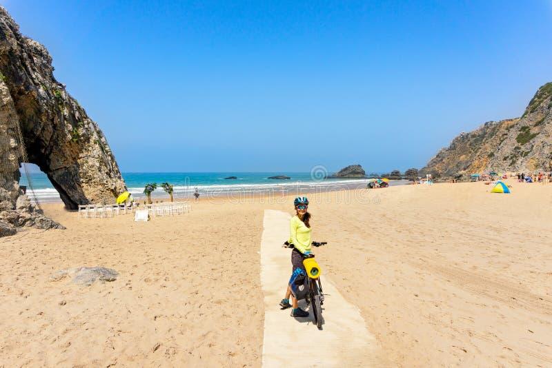 De volwassen aantrekkelijke vrouwelijke fietser met haar fiets stelt en glimlacht op een oceaanstrand Portugal, Europa royalty-vrije stock afbeeldingen