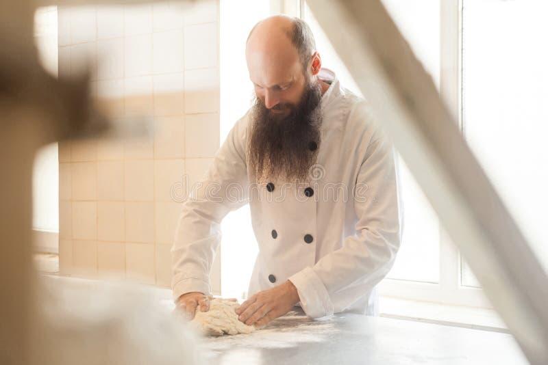 De volwassen bakker met lange baard in witte eenvormige status in zijn werkplaats en bereidt het brooddeeg met handen voor kneden stock afbeelding