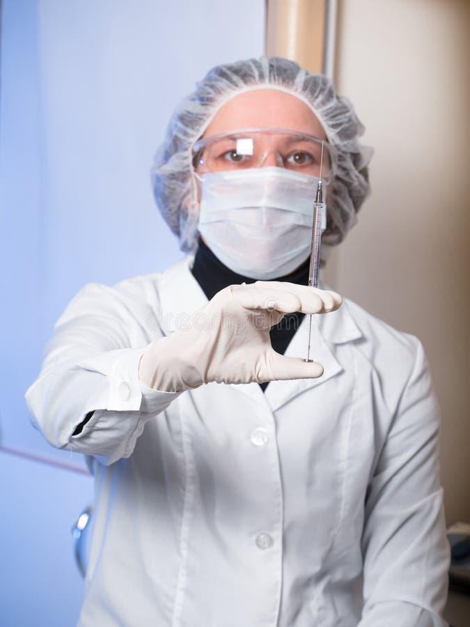 De volwassen beschermende glazen van de vrouwenclose-up en medische maskerholding in zijn spuit van het handglas stock fotografie