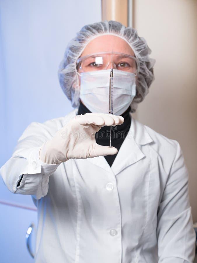 De volwassen beschermende glazen van de vrouwenclose-up en medische maskerholding in zijn spuit van het handglas royalty-vrije stock foto's