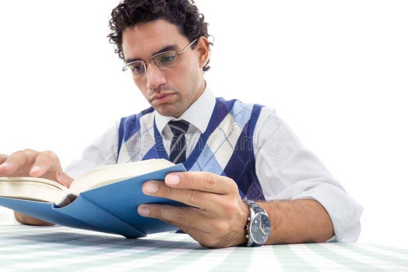 De volwassen ernstige mens die in trui met glazen en leest boe-geroep zitten stock fotografie