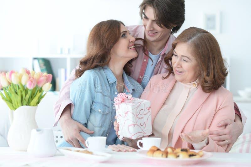De volwassen kinderen wensen de bejaarde moeder geluk stock foto