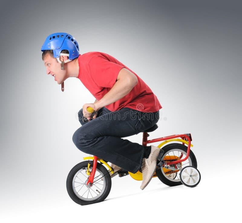 De volwassen mens gaat op een fiets van kinderen royalty-vrije stock afbeelding