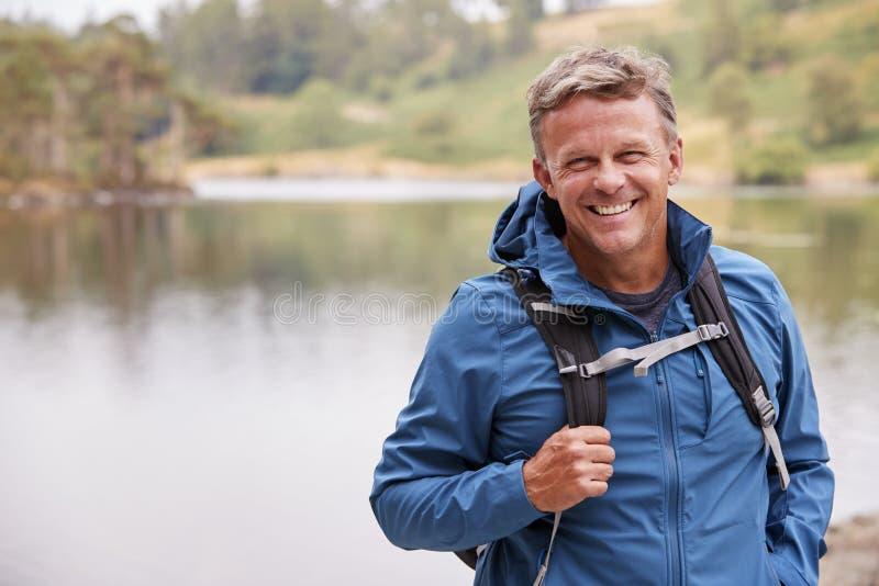 De volwassen mens op een kampeervakantie die zich door een meer bevinden die aan camera glimlachen, sluit omhoog, Meerdistrict, h royalty-vrije stock afbeelding