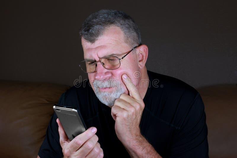 De volwassen Mens overweegt Zijn Mobiele Telefoon royalty-vrije stock afbeelding