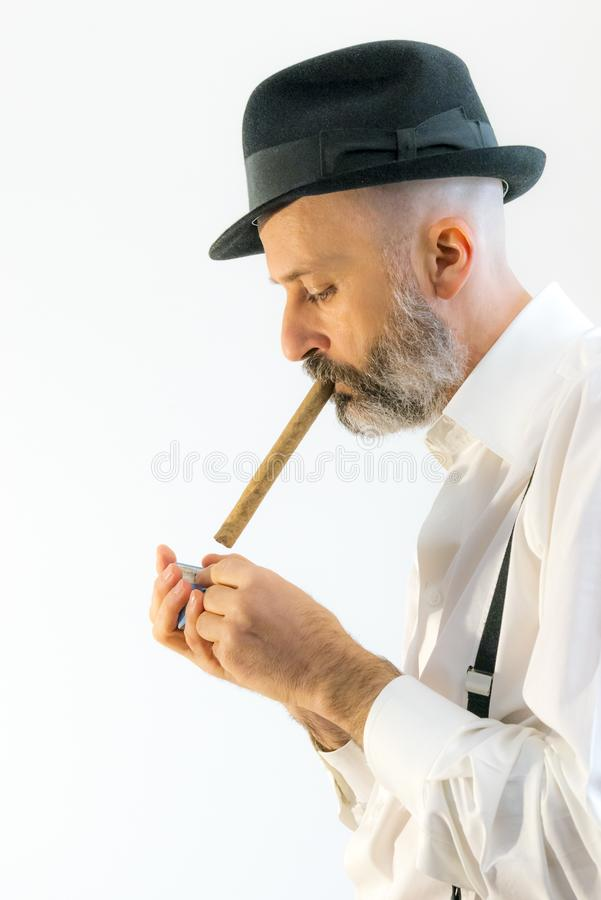 De volwassen mens rookt sigaar met hoed royalty-vrije stock afbeelding
