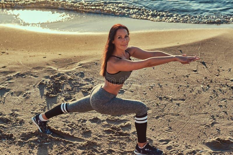 De volwassen mooie geschiktheidsvrouw in een grijze sportkleding die verschillende yoga uitoefenen oefent dichtbij een water uit royalty-vrije stock afbeelding