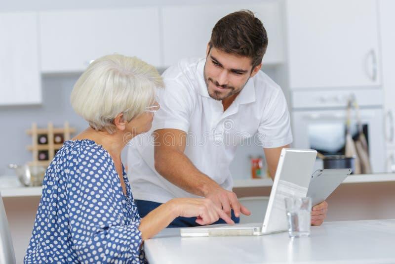 De volwassen oma die van het kleinzoononderwijs computer met behulp van stock afbeeldingen