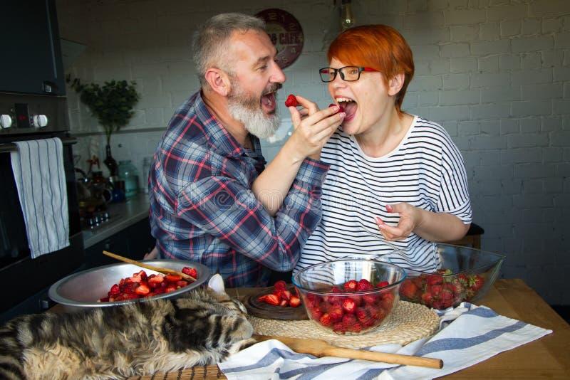 De volwassen de paarman en vrouw pellen en snijden aardbeien voor aardbeijam, voeden elkaar, lachen en hebben pret, Maine Coon stock afbeelding