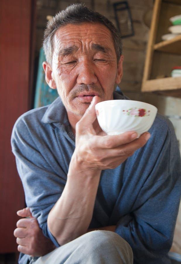 De volwassen persoon de inwoner van Azië drinkt thee stock afbeelding
