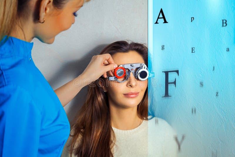 De volwassen vrouw controleert visie in een oftalmoloog met correctief stock afbeeldingen